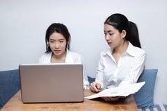 Jeune femme d'affaires deux asiatique travaillant ensemble sur un ordinateur portable au bureau Photo stock