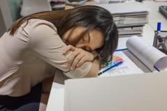 Jeune femme d'affaires dormant sur le bureau images stock