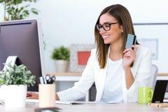 Jeune femme d'affaires employant la carte de crédit sur la boutique en ligne Photographie stock