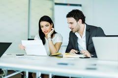 Jeune femme d'affaires et un homme d'affaires regardant un papier tandis que s images stock