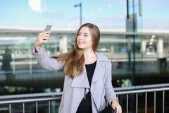 Jeune femme d'affaires européenne faisant le selfie par le smartphone près de la mallette et de l'aéroport Photo libre de droits