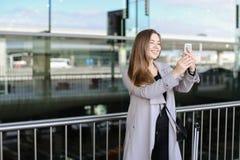 Jeune femme d'affaires faisant le selfie par le smartphone près de la mallette et de l'aéroport Photos libres de droits