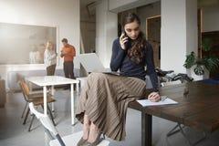 Jeune femme d'affaires faisant un appel tout en se reposant sur le bureau et le travail images stock