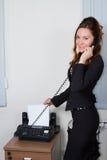 Jeune femme d'affaires faxant le document photos libres de droits