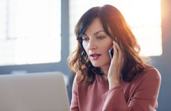 Jeune femme d'affaires focalisée dur au travail dans un bureau moderne photos stock
