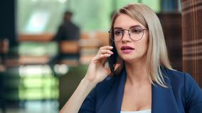 Jeune femme d'affaires focalisée en verres parlant utilisant le smartphone au fond moderne de bureau banque de vidéos
