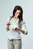 Jeune femme d'affaires gaie regardant sa montre sur le poignet Photo stock