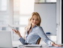 Jeune femme d'affaires heureuse détendant avec l'instrument dans le bureau Images libres de droits