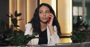 Jeune femme d'affaires heureuse parlant au téléphone tout en se reposant en café Elle est souriante et buvante du café Belle fill clips vidéos