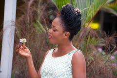 Jeune femme d'affaires heureuse tenant une fleur blanche dans sa main photos stock