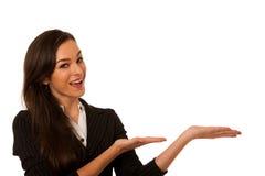Jeune femme d'affaires indiquant l'espace de copie, montrant un produit i Photographie stock libre de droits