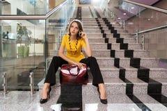 Jeune femme d'affaires invitant le téléphone dans le bureau Images stock