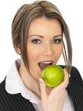 Jeune femme d'affaires mangeant Apple vert juteux mûr frais Photographie stock libre de droits