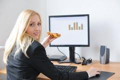 Jeune femme d'affaires mangeant de la pizza Photos libres de droits