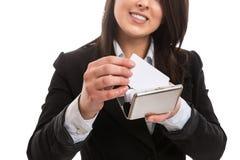 Jeune femme d'affaires mettant la carte de visite professionnelle de visite dans le support Photographie stock