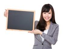Jeune femme d'affaires montrant le blanc du tableau Image stock