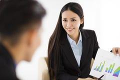 Jeune femme d'affaires montrant le graphique sur le diagramme dans le bureau images stock