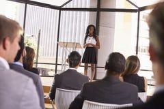 Jeune femme d'affaires noire présent le séminaire à une assistance photo libre de droits