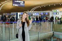 Jeune femme d'affaires parlant par le smartphone au hall d'aéroport, au manteau gris de port et montrant correct Photo libre de droits