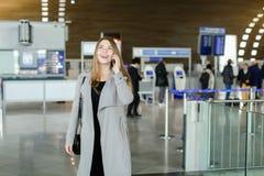 Jeune femme d'affaires parlant par le smartphone au hall d'aéroport, au manteau gris de port et au sac Image libre de droits