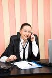 Jeune femme d'affaires parlant par le téléphone dans le bureau Photographie stock