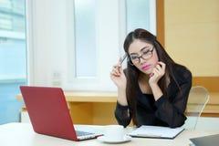 Jeune femme d'affaires pensant avec un stylo à disposition à son workplac Photographie stock