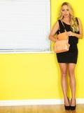 Jeune femme d'affaires portant une robe noire et des chaussures de talon haut tenant un sac à main rose Photo stock
