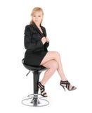 Jeune femme d'affaires posant sur une présidence de bar au-dessus du fond blanc Photographie stock libre de droits