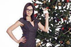 Jeune femme d'affaires près de l'arbre de nouvelle année tenant la carte de visite professionnelle de visite Photos stock
