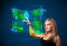 Jeune femme d'affaires pressant le panneau moderne de technologie avec le doigt Image stock