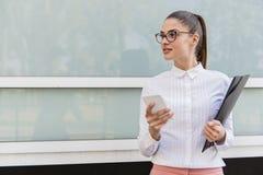 Jeune femme d'affaires réussie à l'aide du smartphone et tenant le docu photo stock