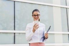 Jeune femme d'affaires réussie à l'aide du smartphone et tenant le docu photos stock