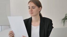 Jeune femme d'affaires Reading Documents au travail banque de vidéos
