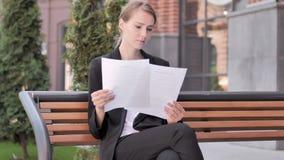 Jeune femme d'affaires Reading Documents tout en se reposant extérieur sur le banc clips vidéos