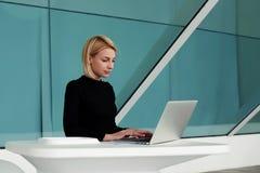 Jeune femme d'affaires recherchant l'information dans l'Internet par l'intermédiaire de l'ordinateur portable pendant la pause Image stock