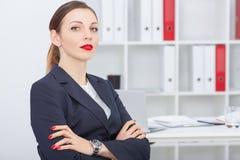 Jeune femme d'affaires regardant avec confiance l'appareil-photo dans la perspective des bureaux photographie stock