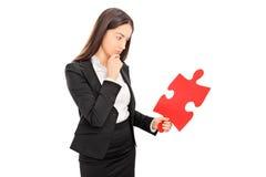 Jeune femme d'affaires regardant le morceau d'un puzzle Photographie stock