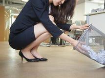 Jeune femme d'affaires regardant par la poubelle de vieux papiers dans le bureau Photographie stock libre de droits