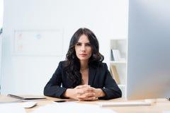 jeune femme d'affaires sérieuse s'asseyant au lieu de travail et au regard Image stock