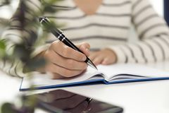 Jeune femme d'affaires s'asseyant à la table et écrivant dans le carnet O photo stock