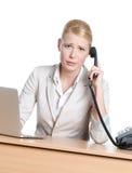 Jeune femme d'affaires s'asseyant à un bureau avec le combiné téléphonique de téléphone photographie stock