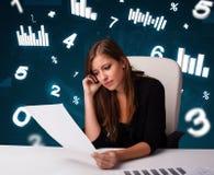 Jeune femme d'affaires s'asseyant au bureau avec des tableaux et des statistiques photos libres de droits