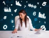 Jeune femme d'affaires s'asseyant au bureau avec des tableaux et des statistiques photographie stock