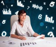 Jeune femme d'affaires s'asseyant au bureau avec des tableaux et des statistiques photos stock