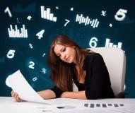 Jeune femme d'affaires s'asseyant au bureau avec des tableaux et des statistiques images libres de droits