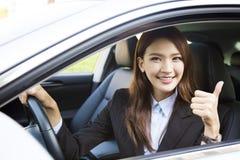 Jeune femme d'affaires s'asseyant dans la voiture et montrant des pouces  Photo stock