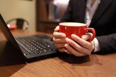 Jeune femme d'affaires s'asseyant dans le café à la table en bois, café potable Sur la table est l'ordinateur portable Photographie stock libre de droits
