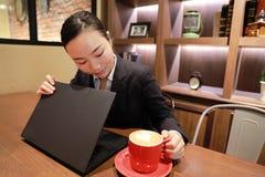 Jeune femme d'affaires s'asseyant dans le café à la table en bois, café potable Sur la table est l'ordinateur portable Images stock