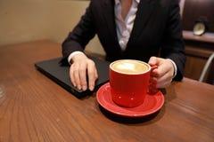 Jeune femme d'affaires s'asseyant dans le café à la table en bois, café potable Sur la table est l'ordinateur portable Photos stock