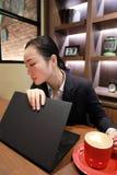 Jeune femme d'affaires s'asseyant dans le café à la table en bois, café potable Sur la table est l'ordinateur portable Photo libre de droits